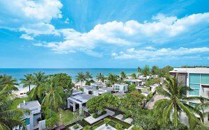 Aleenta Phuket Hotel, vista del resort sulla spiaggia con palme a bordo mare.