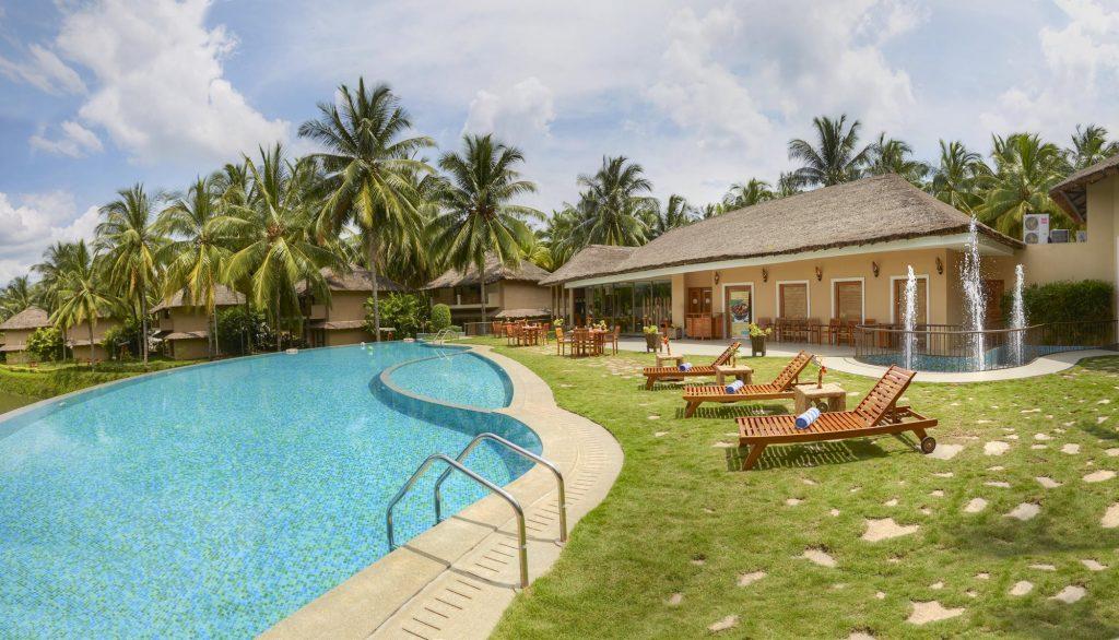 Camere con vista su giardino, palme e piscina del Coco Lagoon by Great Mountain Resort in Pollachi, Kerala