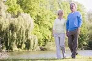 Una coppia di anziani sorridenti cammina felice nella natura e nel verde.