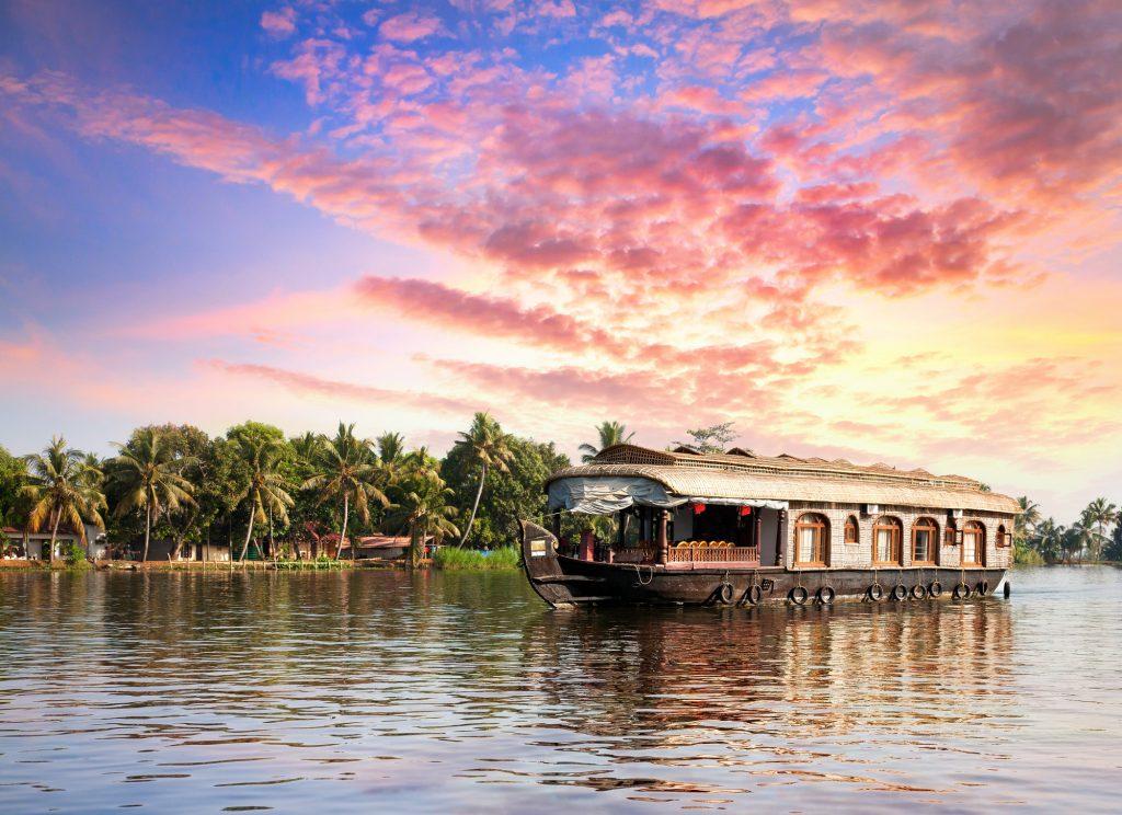 Casa galleggiante nelle backwaters vicino alle palme in un bellissimo tramonto ad Alappuzha, Kerala, India
