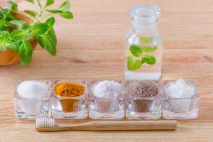 Colluttorio naturale alternativo con menta, dentifricio allo xilitoro, sale dell'Himalaya, curcuma, cenere, olio di cocco, spazzolino in legno.