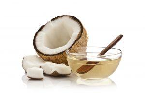 Ciotola piena di olio di cocco con mezzo cocco e piccoli pezzi a fianco su sfondo bianco.