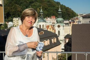 Primo piano della dottoressa Sárová con sfondo della città.