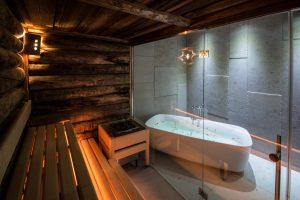 Vasca da bagno con petali di fiori, luci soffuse, una panca in legno, trattamenti di cura e prevenzione.