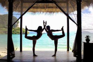 Due ragazze in posizione yoga sulla veranda a bordo mare e spiaggia del Paradise Koh Yao in Thailandia.