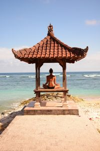 Isola di Bali- donna sulla spiaggia che pratica yoga