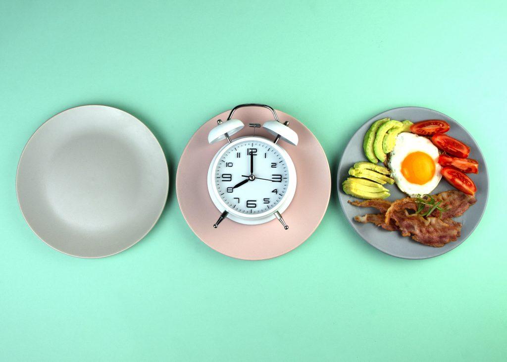 Piatti con orologio e pranzo a base di avocado, uova, bacon e pomodori