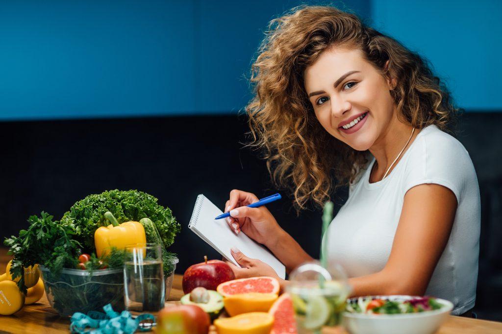 Donna sorridente prende nota su un quadernetto di fronte a una tavola imbandita di frutta e verdura
