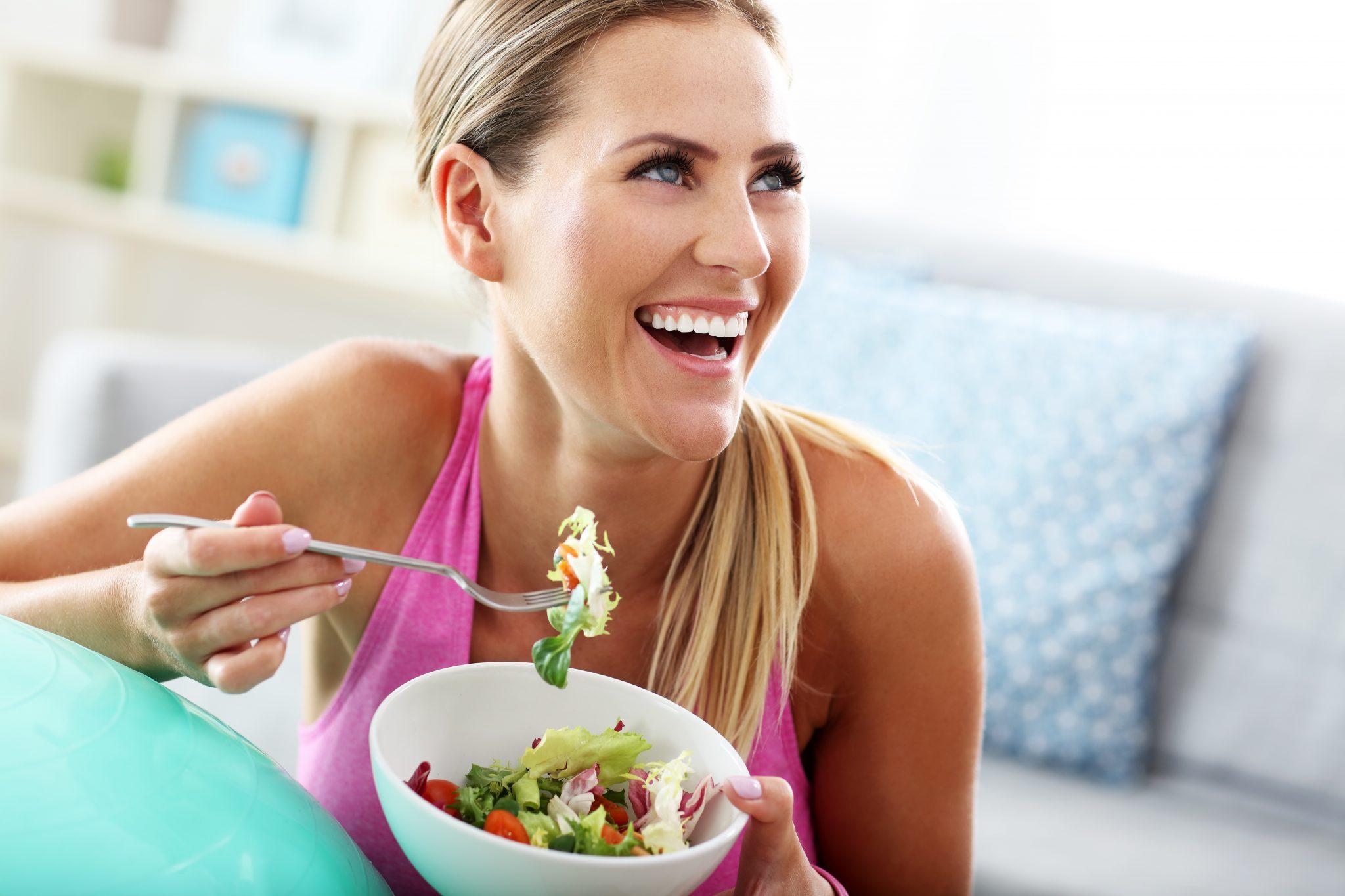Donna sorridente mangia un'insalata da una ciotola bianca