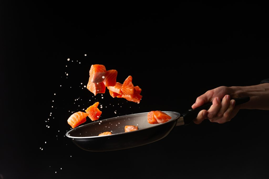 Salmone viene cucinato in padella, sfondo nero