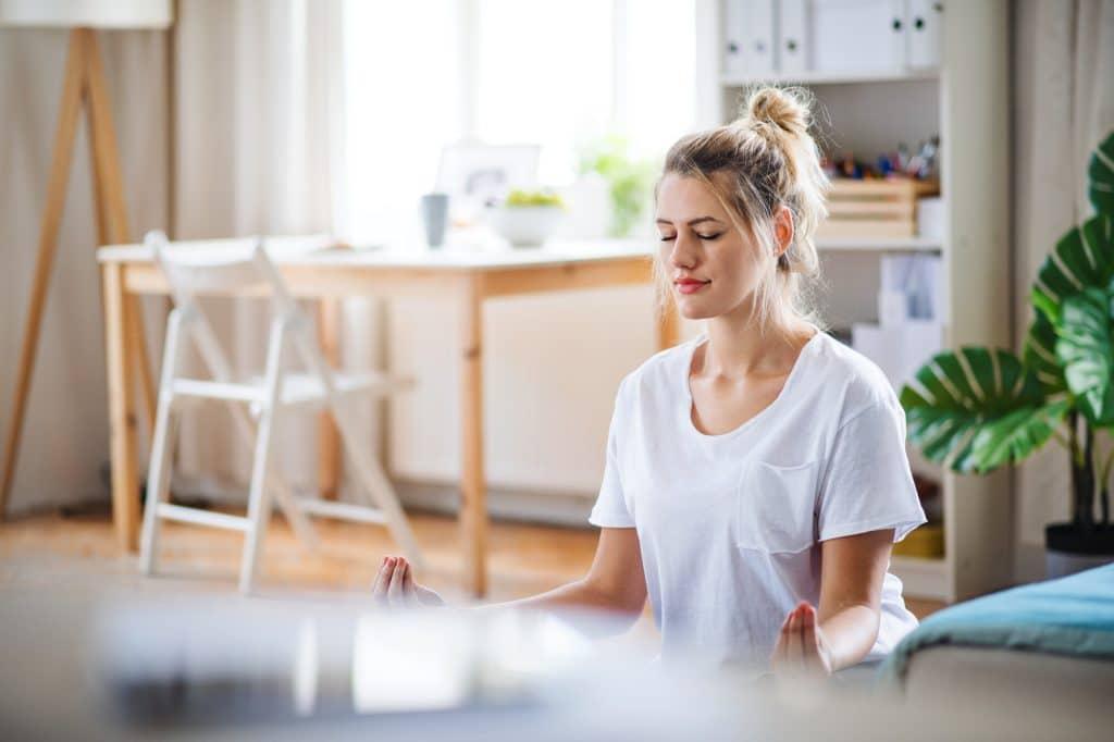 Donna che medita e fa yoga in casa.