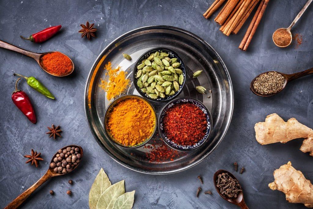 Spezie varie su piatto d'argento, tra cui cardamomo, cannella, zenzero, chilli, anice