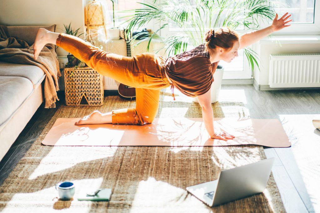 Donna fa yoga a casa seguendo un tutorial sul computer